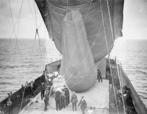A 'Drachen' type balloon is held steady aboard the SS Manica, as a spotter prepares to climb into the basket, Gallipoli 1915. Image courtesy Imperial War Museum.