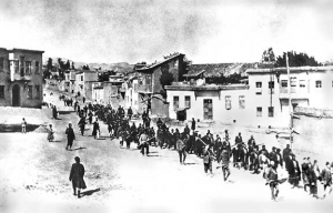 Armed Turkish soldiers march Armenians to prison in Mezireh, April 1915. Image in public domain.