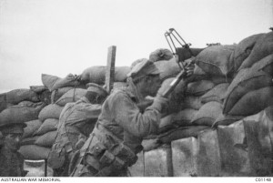 A soldier uses a periscope rifle in a trench while his mate observes for him through a periscope, Gallipoli Peninsula  1915. Image courtesy Australian War Memorial.