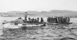 A launch tows a raft carrying artillerymen and guns out to waiting ships during the evacuation of Gallipoli Peninsula, December 1915. Image courtesy Australian War Memorial.