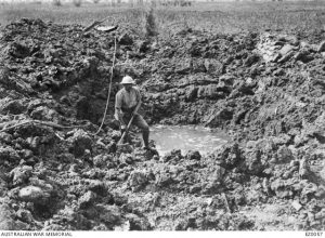 A soldier beside a crater made by a German minenwerfer (trench mortar) bomb, Cordonnerie Farm, France, 30 May 1916. Image courtesy Australian War Memorial.